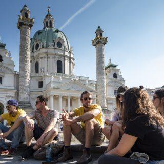 Wien Führungen - Wien Challenge 23 Bezirke - Wien Grätzl Führungen, Gruppe von Touristen und Fremdenführer sitzen vor der Karlskirche